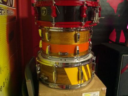 I'm just getting started into customizing drums, its becoming a passion :) My first pieces were snares and then i made my way to completing a kit... My kit consist of 20'x22 bass, 12'x8'tom, 14'x16'tom, and 16'x16'tom,12'x6' custom snare, MCS cymbals, blue hardware and flat black paint job:) Still learning, but I love it... My shells were maple, manufactured by ddrum and everything done on them was horrible quality. I removed the wrap which had 3 thick glue strips on each shell, I used a heat gun to safely remove the glue strips with out scratching the surface of the wood. Sanded everything down to remove all the filler I had to put in because the shells were not well put together. There were huge gaps between the seems of the shell, opened up the pores and then wiped clean all the debris. This time around on my set instead of staining I wanted to paint. I used an automotive grade primer and paint. The automotive grade paint was amazing covered great and super easy to use shooting it out of a hvlp gun (if anyone is going this route make sure you have done your research, because you will need the right air compressor and tools to get the best finishes.) I added a very cool touch by getting a 5 meter strip of led lights which had an adhesive side that glued to the inside of my bass drum, i ran the plug out of the air vent and added a very cool touch. You can find these on ebay for $30 comes with a remote to change colors... All in All looks very professional so I'm happy :) Kevin Penner RevKev customs